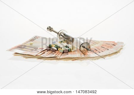 Fan from fifty euros and medical syringe. Many mass currency isolated on white background. Euro cash. Money for the purchase of medicines drugs or narcotic. Bill needle tablets and pills