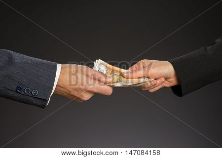Business people hands and fifty euros banknotes isolated gray background. Give a money bribe. Corruption concept. Man and woman hand