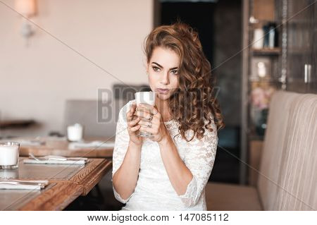 Beautiful girl 20-24 year old holding cup of coffee sitting in cafe.