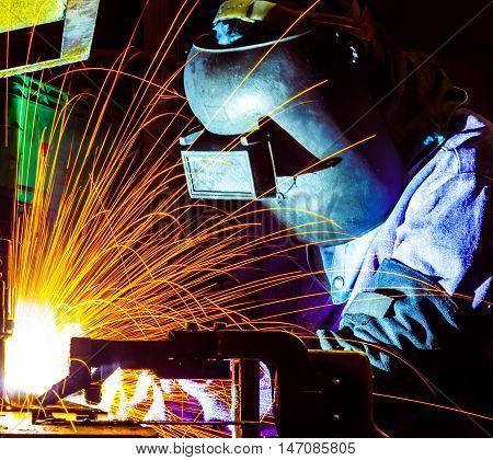 welder welding Industrial automotive part in factory with fire spark