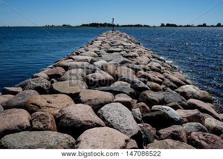 Embedded stones. Rocky beach peaceful sea harbor. Mole in Munalaid Estonia. Baltic sea Europe