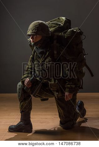 Unarmed woman with camouflage on one knee. Young female soldier observe with binoculars and backpack. War military army people concept