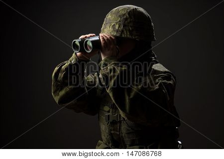 Portrait of unarmed woman with camouflage. Young female soldier observe with binoculars. War military army people concept