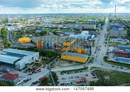 Tyumen, Russia - May 19, 2015: Aerial view on Permyakova street with TV tower. On foreground: plant of metalprofile production, Ochakovo brewery, Perestroyka trade center, Construction yard shop