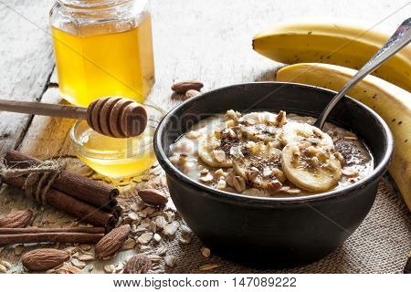 oatmeal porridge with banana nuts honey and spices in ceramic bowl with a spoon. healthy breakfast. top view