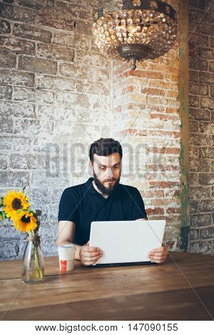 Handsome young man is sitting in a coffee and having video chat with his girlfriend by using web-camera on his laptop. Relationship and communication concept. Distant relationship