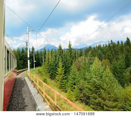 View of High Tatras mountains from window of speeding train on cog railway during way from Strba station to Strbske Pleso station.