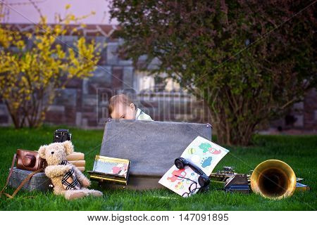 Little boy opened the suitcase and looking into it. Nearby the toy bear the camera phone a suitcase and a pipe lies. Photo in retro style