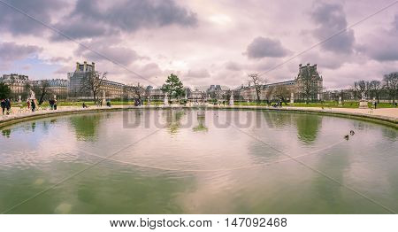 Louvre Museum garden in February - Panoramic view with the Louvre garden with its big artesian fountain and the famous Louvre Museum building in background. Picture captured in Paris France