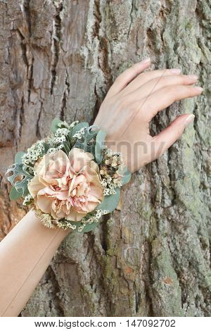 Orange and green wrist corsage on a hand