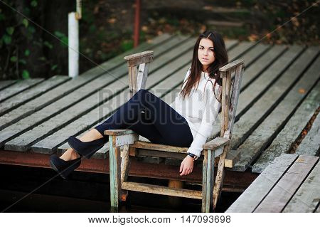 Beautiful brown-eyed brunette with long hair tousled by the wind, a white blouse, dark blue leggings and trendy shoes on a high platform, sitting on wooden stairs at the pier over the water.