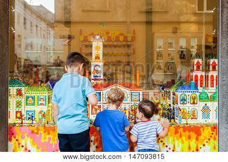LVIV, UKRAINE - AUGUST 19, 2016: Conceptual photography of unidentified children outside the shop with sweets. Storefront caramel products. Candy shop.