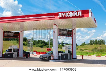 BOROVICHI RUSSIA - JUNE 26 2016: Lukoil gas station with fueling cars. Lukoil is the largest privately owned oil and gas company in the world by proved oil reserves