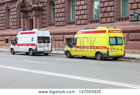 ST. PETERSBURG RUSSIA - JULY 31 2016: Emergency ambulance cars with blue flashing light on the roof parked up on the city street. Text in russian: