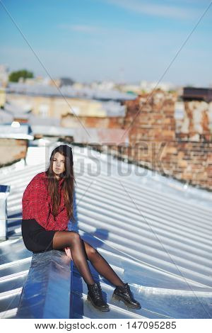 Portrait of thoughtful courageous young girl sitting on the visor iron roof of high-rise buildings.