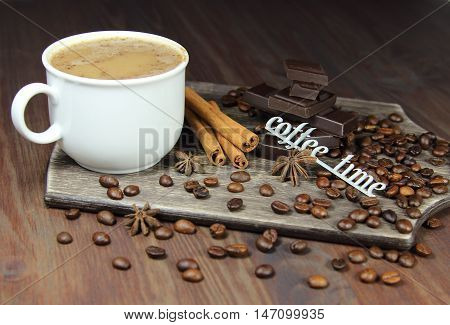 cup of coffee with chocolate, coffee grains, an anisetree, cinnamon and the inscription coffee time