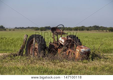 Abandoned and rusty vintage tractor in a field.