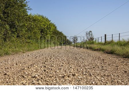 A long open gravel back road sidelined by barb wire fence.