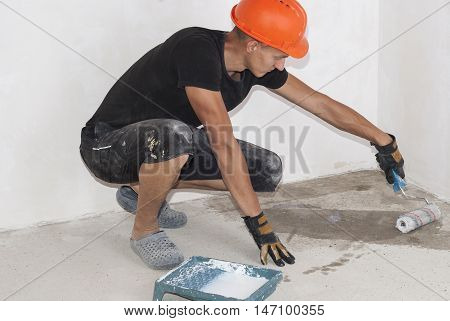 Worker Applies Primer On The Floor