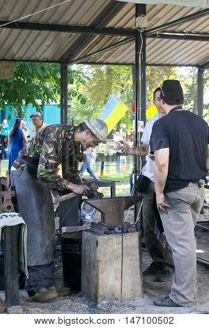 Myrgorod Ukraine - August 20 2016: Blacksmith at work on the festival of blacksmiths