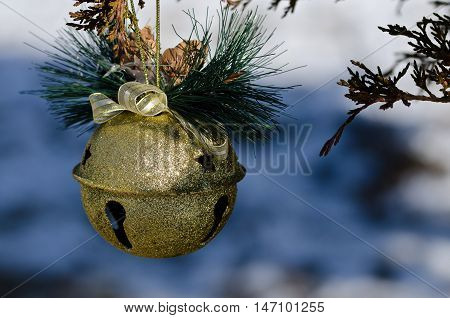Golden Sleigh Bell Christmas Ornament Decorating an Outdoor Tree