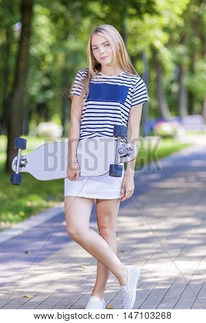Teenager Lifestyle Concepts. Happy Smiling Caucasian Blond Teenager Girl Posing With Longboard Outdoors. Vertical Shot