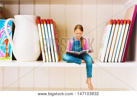 Little girl sitting on bookshelf and reading interesting story book. Education and school, study and literature.