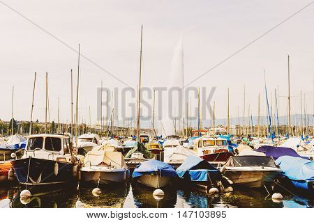 Geneva port with boats and Jet d'eau on background on a very sunny day, toned image