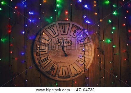 Wooden hours on a wooden wall show five minutes about new year.