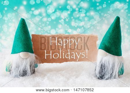 Christmas Greeting Card With Two Turqoise Gnomes. Sparkling Bokeh Background With Snow. English Text Happy Holidays