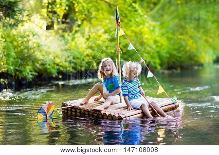 Two children on wooden raft catching fish with a colorful net in a river and playing with water on hot summer day. Outdoor fun and adventure for kids. Boy and girl in toy boat. Sailor role game. poster