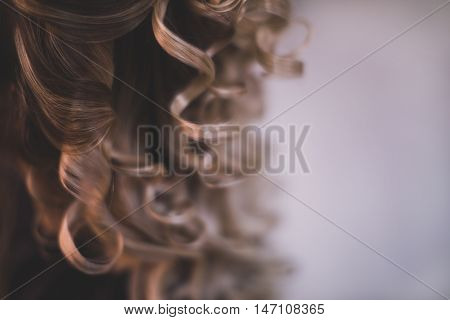 Ringlets of hair of the brunette close up. Background with place for your message