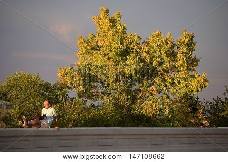 Denver, CO - September 12, 2016:  Person resting with his dog at Inspiration Point which is a place in Inspiration Park where people can enjoy views of Denver and the Rocky Mountains taken in Denver, CO.