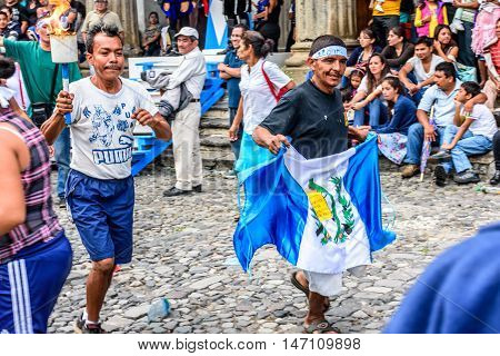 Antigua Guatemala - September 14 2015: Locals run by city hall with Guatemalan flag & lit torches during Guatemalan Independence Day celebrations