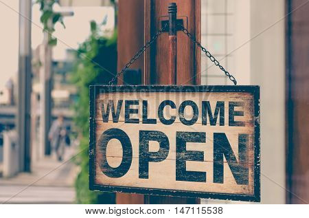 Wood open sign board hanging on shop door