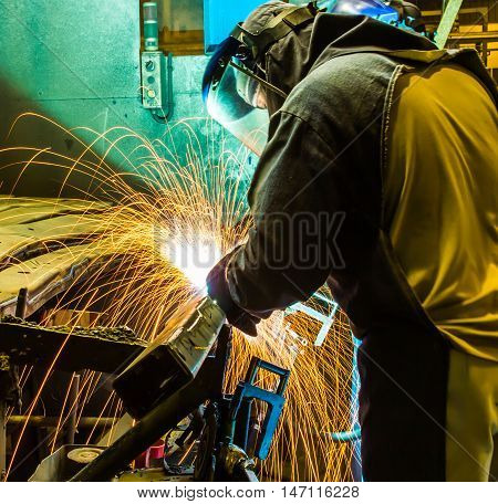 The worker grinding metal in car manufacturing plant poster