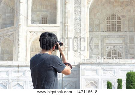 Close-up Of Asian Photographer Taking Pictures Of Taj Mahal