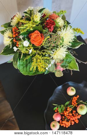 bouquet of apple Chrysanthemum rowan stonecrop anisetree phlox near edible ingredients on plate