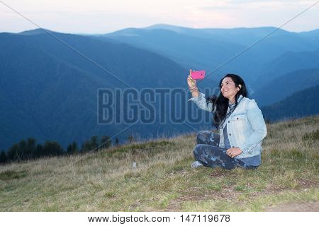 Cheerful woman doing selfie by phone mobile in the moountains