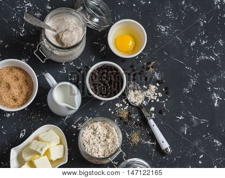 Baking background. Flour sugar butter rolled oats eggs chocolate chips on a dark background. Baking ingredients