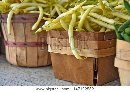 Raw yellow beans in wooden produce box and bushel basket at the farmer's market