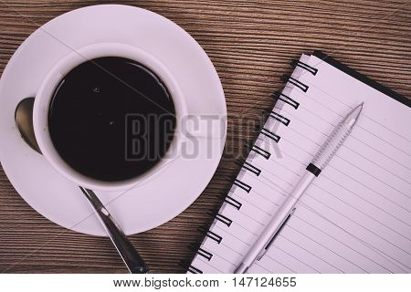 Cup Of Black Coffee And Notebook On Wooden Surface Vintage Retro Filter.