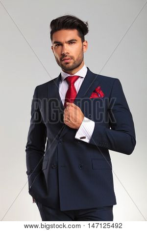elegant business man in double breasted suit looking up and thinking on grey studio background