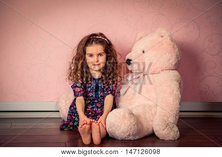 Little Girl Plays Big Soft Bear In A Baby Pink Room