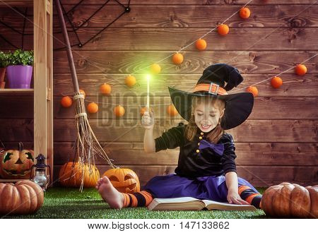 Happy Halloween! Cute cheerful little witch with a magic wand and book of spells. Beautiful child girl in witch costume sitting on grass, conjuring and laughing.