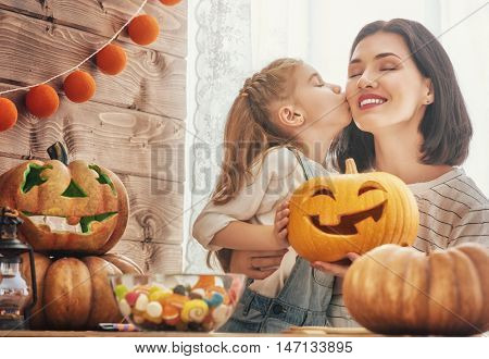 Happy halloween! A mother and her daughter carving pumpkin. Happy family preparing for Halloween.