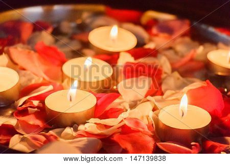 Romantic tea candles in rose petals creating ambiance and warm atmosphere
