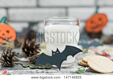 Fresh milk and chocolate cookies on wooden table, white brick wall on background