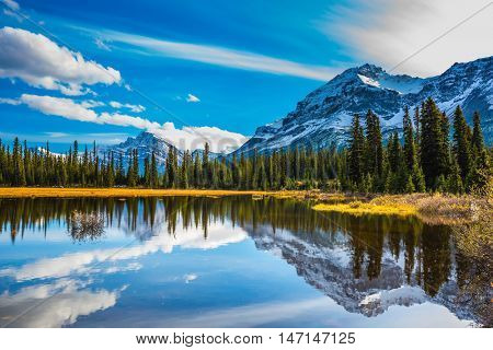 Snow-covered mountains are reflected in smooth water of the lake. Rocky Mountains on a sunny autumn day. The concept of active tourism and ecotourism