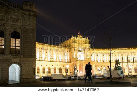 VIENNA, AUSTRIA - NOVEMBER 13, 2015: A young couple in front of Hofburg Palace on heldenplatz at night